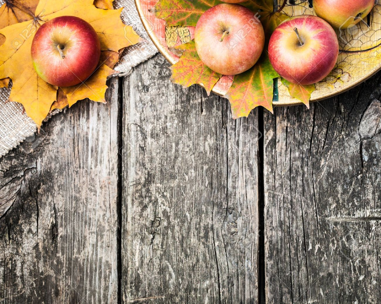 13881900-Autumn-border-from-apples-and-fallen-leaves-on-old-wooden-table-Thanksgiving-day-concept-Stock-Photo