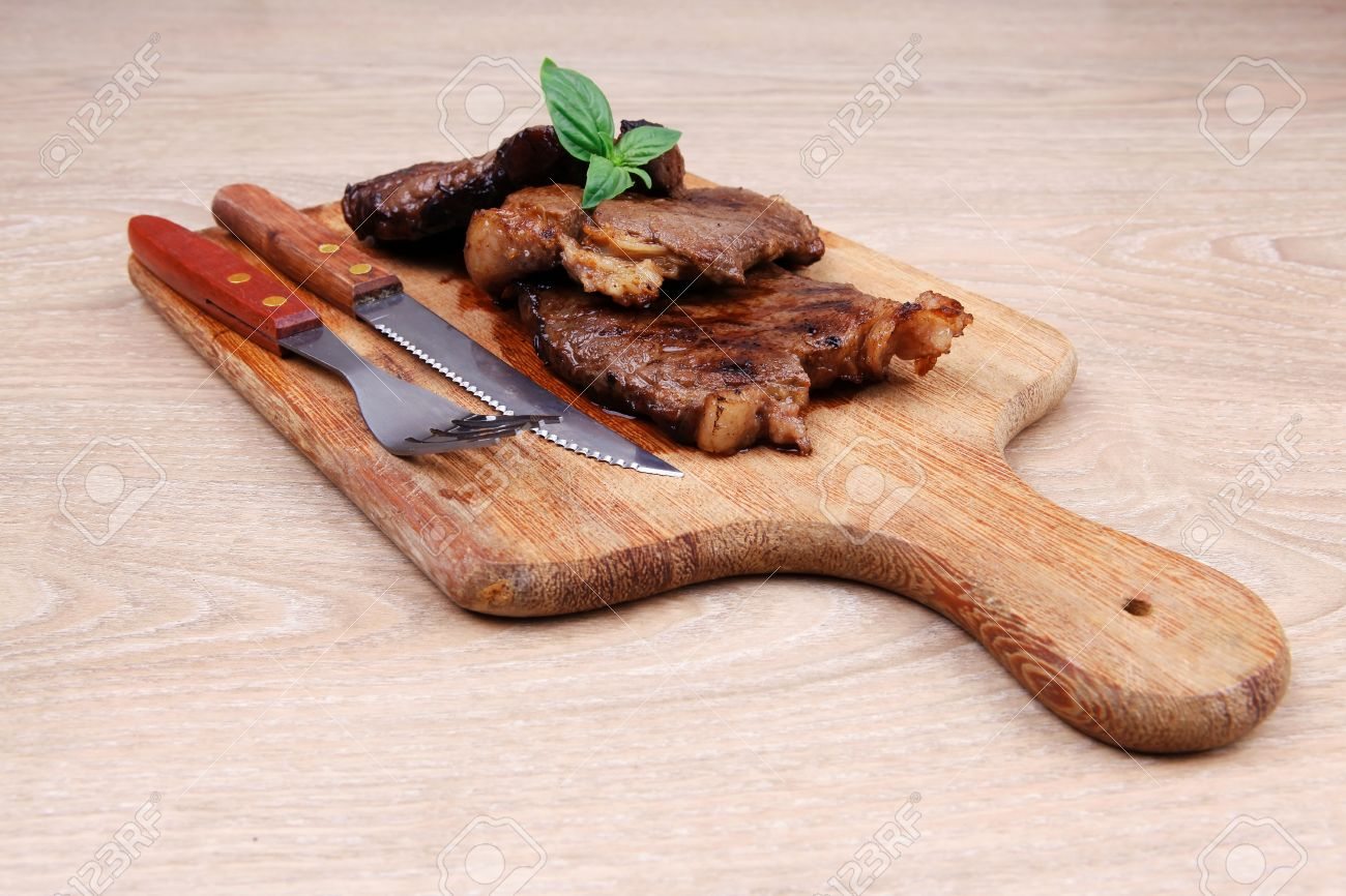 21604990-served-beef-meat-barbecue-on-wooden-plate-with-cutlery-Stock-Photo