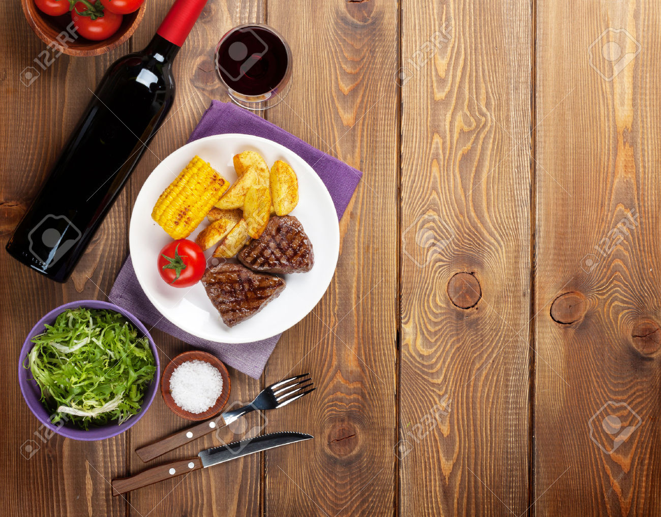 37621241-Steak-with-grilled-potato-corn-salad-and-red-wine-over-wooden-table-Top-view-with-copy-space-Stock-Photo