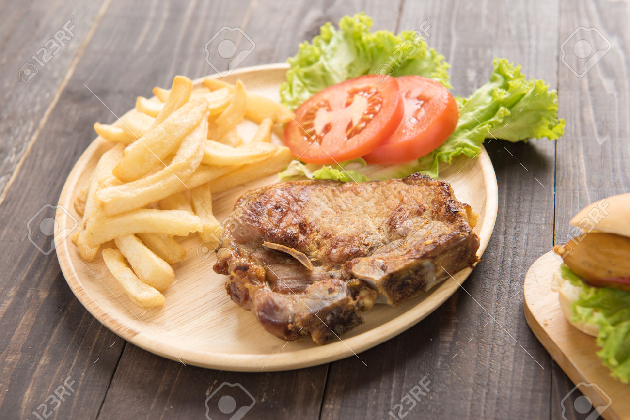 grilled pork chop steak and vegetables with french fries on wood