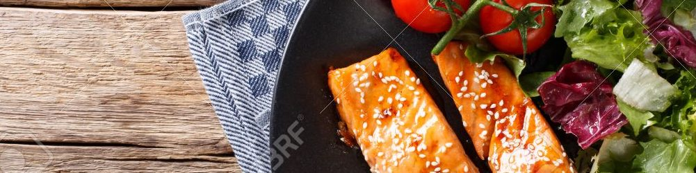 Salmon with sesame seeds in Asian style and fresh salad close-up