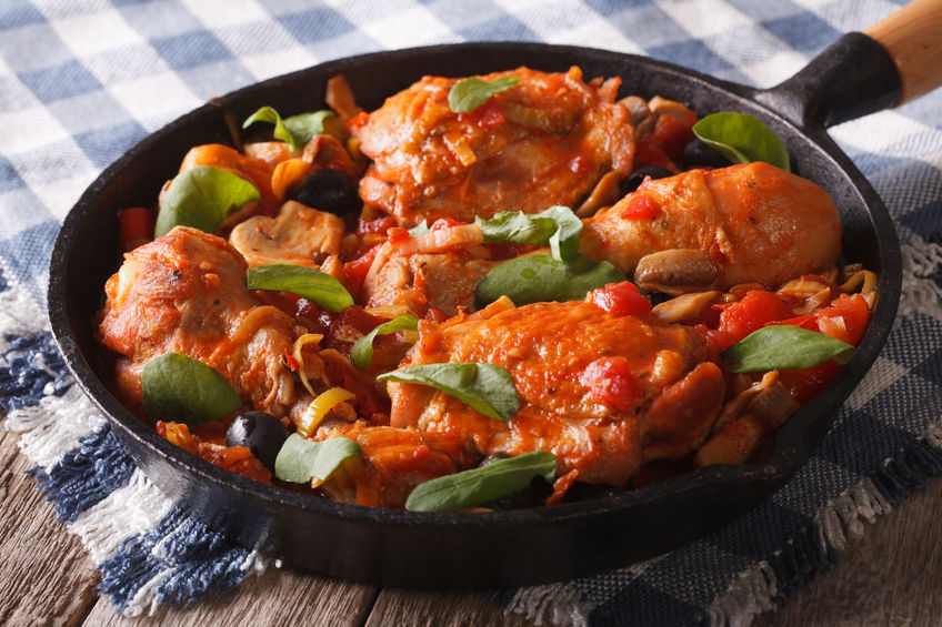 48296165 – chicken with tomatoes and vegetables close-up in a frying pan.